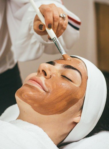 Woman in salon with a mask being painted on her face by an esthetician