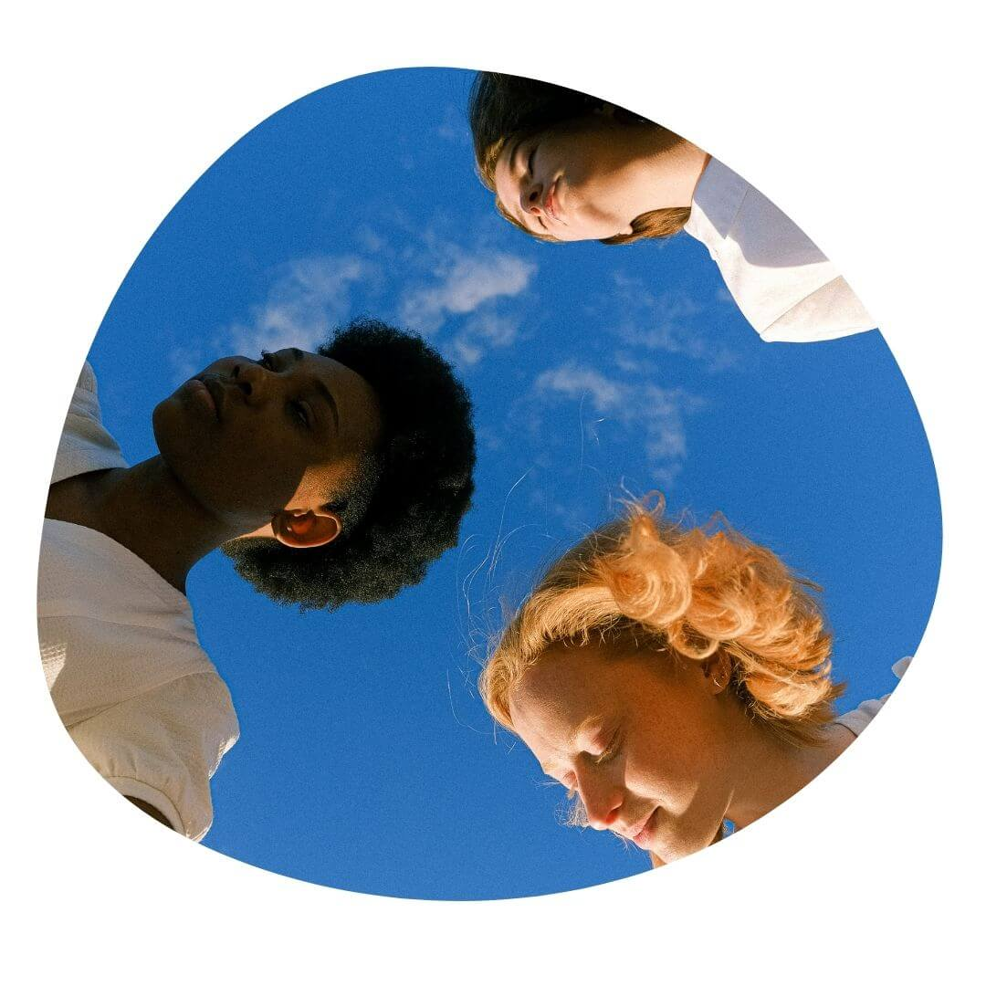 Three women in a circle shot from below with a blue sky in the background
